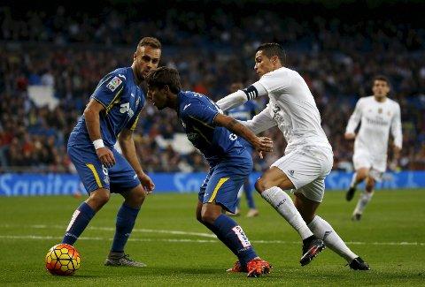 Getafe har en svak statistikk på bortebane mot Malaga. Her er Getafes Damian Suarez i kamp med Real Madrids Cristiano Ronaldo.