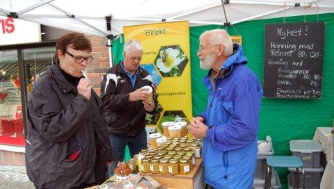 NÆRMAT: Lørdag var det marked i gatene i Sundet. Lokale matprodusenter som birøkter Juul Melvold Minnesund fra Minnesund var på plass. Paul Kjellbakk og Reidun Kirste er imponert over utvalget.