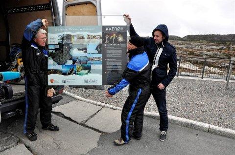 Paul Johan Utheim (fra venstre) og Jørn Kjersheim fra Arkeoplan monterer skiltet. Til høyre Frode Ressem, leder i Averøy Næringsforum.