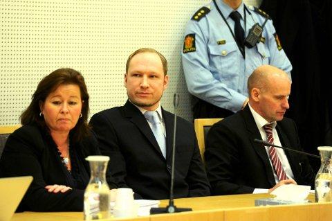 Anders Behring Breivik virket fornøyd da han like etter 12.30 mandag ble ført inn i retten av fire fengselsbetjenter. Han sa ikke noe, men smilte forsiktig i det drøye minuttet fotoseansen varte. Han satte han seg ned ved sine forsvarere, Vibeke Hein Bæra og Geir Lippestad.