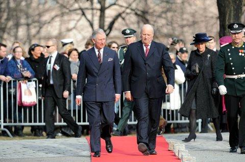 Kong Harald og prins Charles på Akershus festning tirsdag i forbindelse med kransenedleggelse ved nasjonalmonumentet. Camilla Parker Bowles i bakgrunnen.