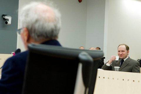 Anders Behring Breivik smiler når professor Ulrik Fredrik Malt forklarer seg i rettsal 250 fredag.