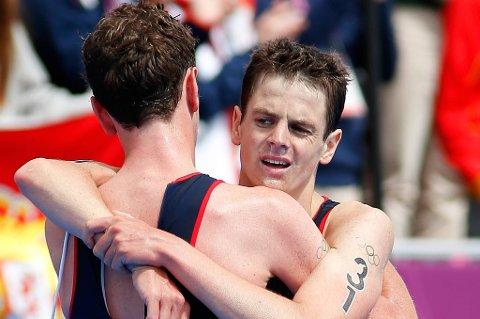 Alistar Brownlee tok gullet i triathlon. Her gratuleres han av lillebror Jonathan.