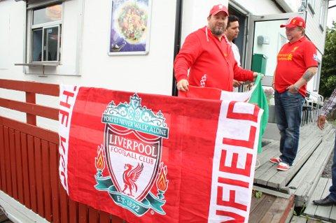 VISER KAMPER: Kløfta har fått sitt eget sted som viser fotball. Bjørn Riiber henger opp Liverpool-flagget sammen med Bihma Sharma og Jonny Bergem.
