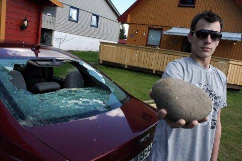 Tony Andresen (19) er rasende etter at vandaler kastet denne store steinen gjennom bakruta på hans parkerte Volvo S40.