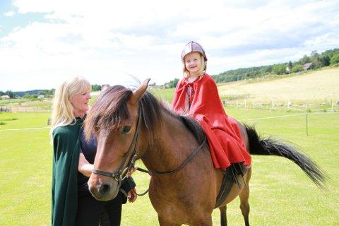 Isabelle Wahl (4) storkoser seg på ryggen til islandshoppa Vænting. Hesteeier Hulda Sigurddadottir følger vaktsomt med fra bakken.