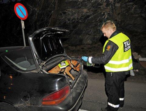 Førstetollinspektør Sverre Hansen og hunden Larry gjennomsøker en bil for narkotika.