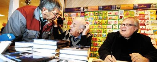 Joralf Gjerstad og Ingar Sletten Kolloen har opplevd en eventyrlig suksess denne bokhøsten. Her signerer de boka for Per Galguften (til venstre) i Overhalla.