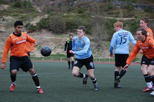 Rune Winther jobber etter ballen innenfor BUILs 16-meter. Russel Karim (t.v.) og Pål Berg (t.h.) prøver å forhindre en LFK-sjanse.