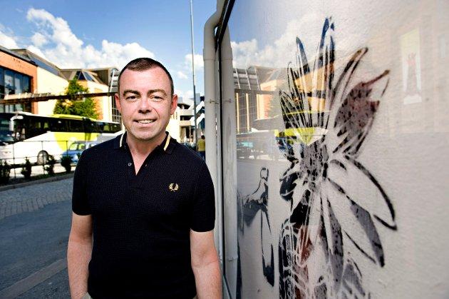 Henning Warloe poserer foran Dolks verk på et kommunalt bygg. Det har kommunen rammet inn for å verne (25.06.2009).