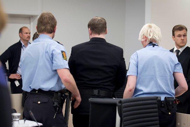 Anders Behring Breivik føres ut av rettssal 250 fredag etter at en av tilhørerne fikk et utbrudd i retten.