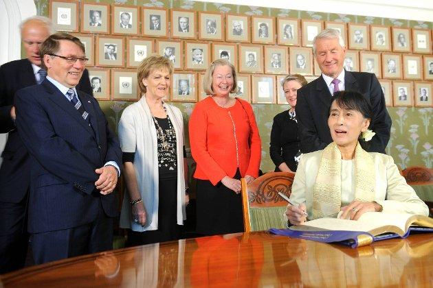 Aung San Suu Kyi er endelig på plass for å sette navnetrekket sitt i den celebre gjesteboken. Det hele ble bivånet av Nobelkomiteens medlemmer Thorbjørn Jagland, Berit Reiss-Andersen, Kaci Kullmann Five, Inger Marie Ytterhorn og Gunnar Stålsett.