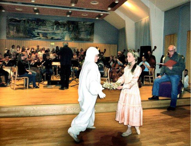 KVITEBJØRN: Prinsessen (Julie Andrea Paulsen) og Kvitebjørn (Maren Nymoen) får det bra sammen. Her står de unge skuespillerne foran orkesteret og barnekoret. Kjolen som Julie Andrea har på seg har ballettlæreren selv brukt, for femti år siden!