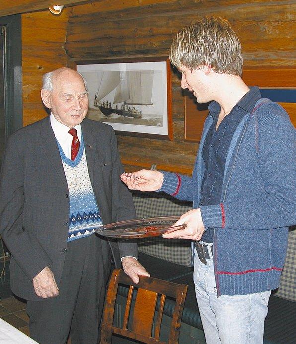 Sigurd Marcussen mottar Det norske Arbeiderpartis æresmedlemsskap for 78 år i partiet.     Partileder i Risør, Henrik  Lindstøl overrekker æresbevisningen.