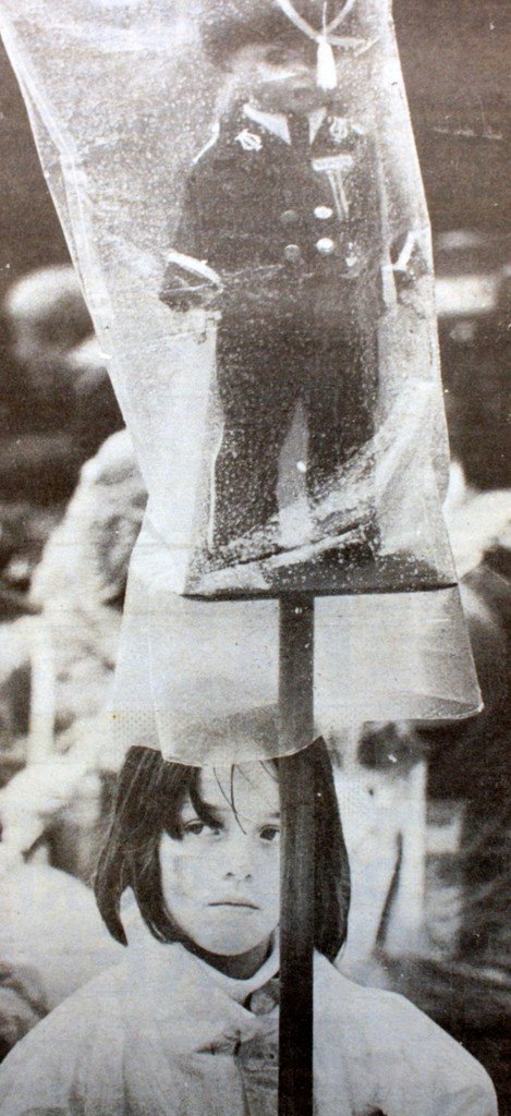 """Innpakket i plast både store og små. Rustet til alle tiders ruskevær på nasjonaldagen. Men så drønnet det 21 ganger fra kanonene på Skansen. Regnet stoppet og hovedprosesjonen kunne gå tørrskodd gjennom buyen. Og da smilte kanskje jenten på bildet også ..."""" Dette sto på forsiden av BA 18. mai 1983, under overskriften """"Salutten stoppet regnet ...!"""" (Foto: BA)"""