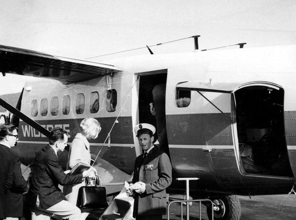 Helgeland Trafikkselskap utførte ekspedering av passasjerer og last for Widerøe på Stokka. Her tar Kåre Andreassen i mot billetter fra passasjerene som går ombord. Bilde utlånt av Kåre Andreassen (Foto: )