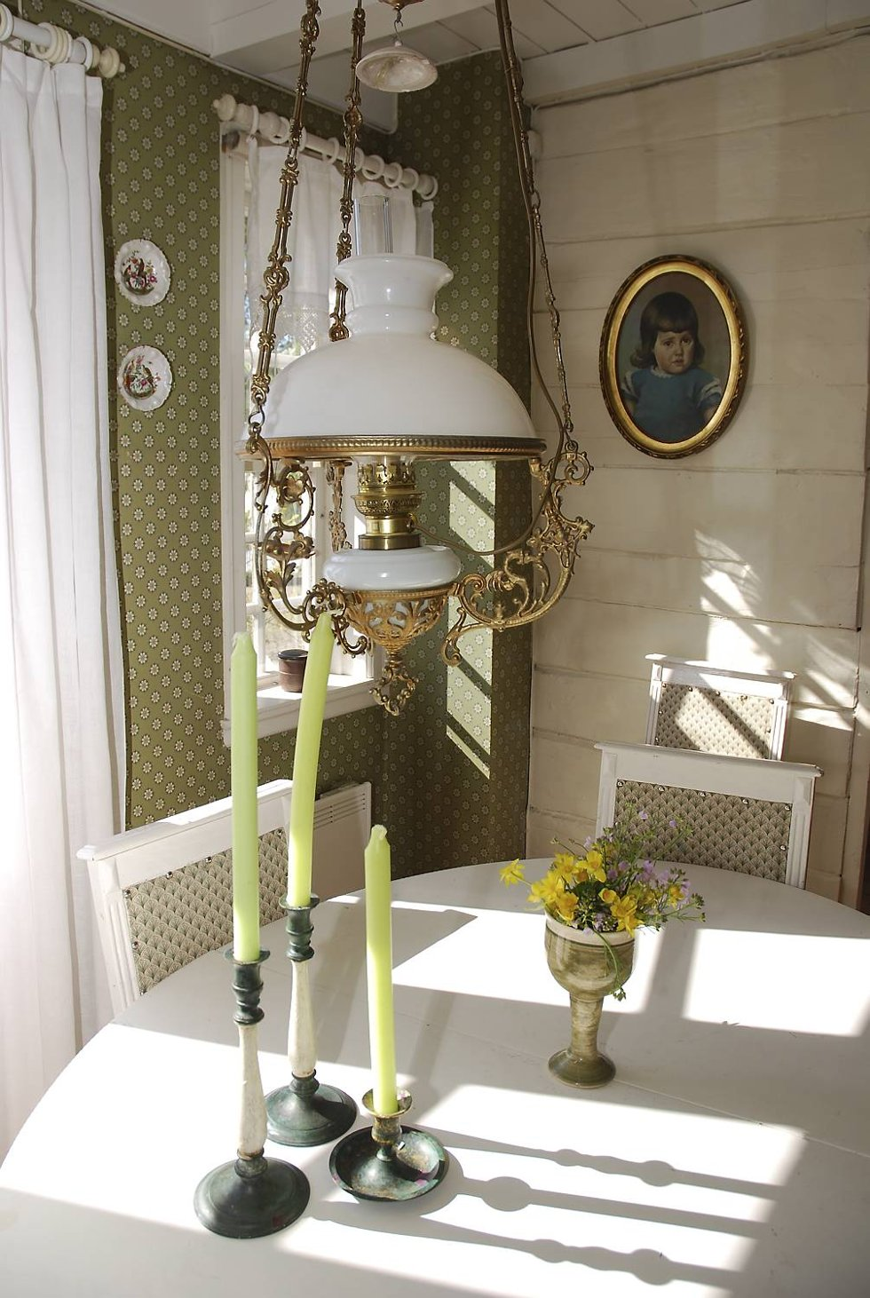 Spisebordet og stolene ble kjøpt på auksjon. Lampen er fra en antikvitetsbutikk. Maleriet er av Kari som fireåring, malt av onkelen hennes. - Det var vanskelig å sitte stille. (Foto: METTE BAKKE)