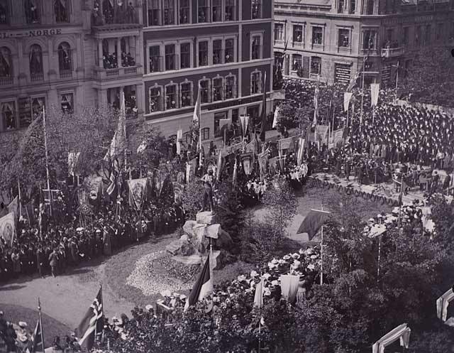 Bildet viser avsløringen av Ole Bull monumentet den 17. mai 1901. Mye folk på plassen rundt og i vinduer og altaner på Hotel Norge og omliggende bygg.              Lagt ut på fotomuseum.bergen360.no av Carl Ole Carlsen (Foto: )