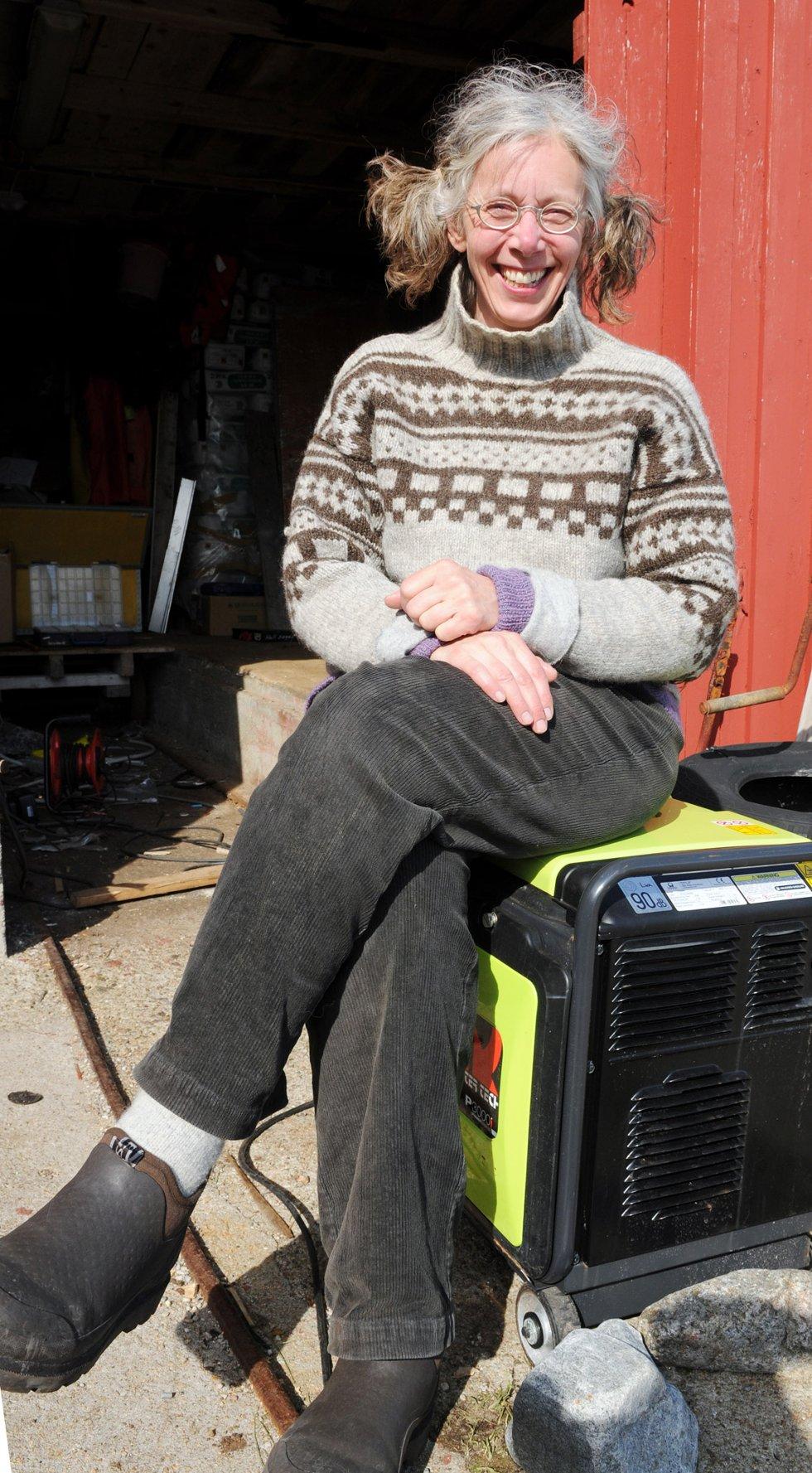 Ellen Marie Hansteensen setter seg demonstrativt på ett av strømaggregatene som ble sendt fra øya nå.