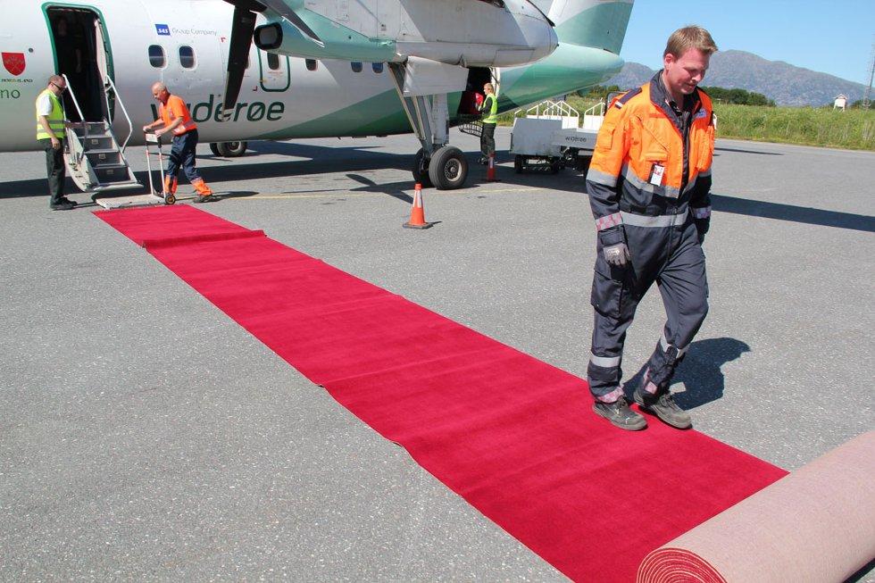 Lufthavnbetjent Øyvind Jensen ruller ut løperen for de første Oslo-passasjerene som ankommer Stokka. (Foto: Morten Hofstad)