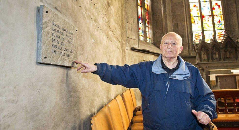 Pensjonist Gunnar Rosenlund viser frem veggen hvor sarkofagen med Magnus Lagabøte angivelig skal ligge. - Dette er det siste mulige stedet han kan ligge, og historien sier at han ble gravlagt her, sier Rosenlund til BA.no.