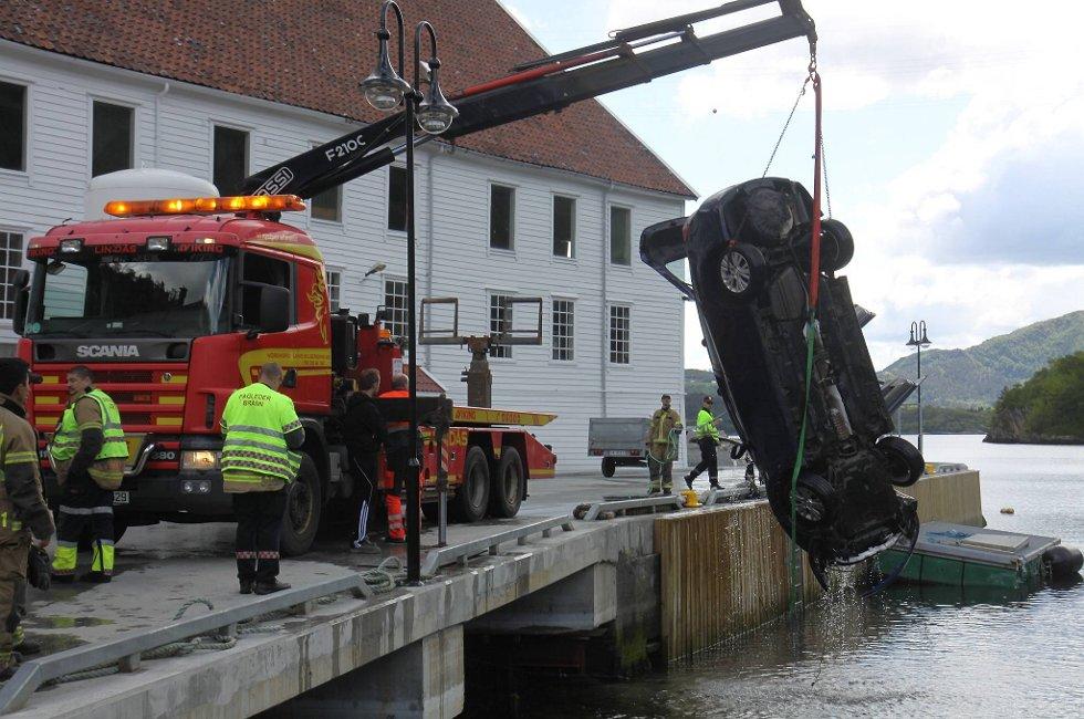 En to år gammel gutt er kritisk skadd etter å ha havnet utenfor kaien i Bjølsvik i denne bilen. Her er en kranbil i ferd med å heve bilen opp fra sjøen.