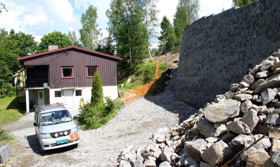 BLE IKKE VARSLET: Eieren av boligen i bakgrunnen, tidligere Fet-ordfører Hallstein Flesland, fikk ikke nabovarsel før Leikvin Boligutvikling A/S satte opp en sju meter høy mur ved siden av huset hans.  BEGGE FOTO: KNUT A. NADHEIM