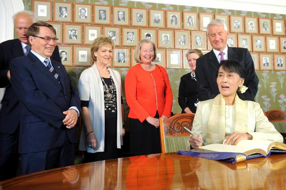 Aung San Suu Kyi er endelig på plass for å sette navnetrekket sitt i den celebre gjesteboken. Det hele ble bivånet av Nobelkomiteens medlemmer Thorbjørn Jagland, Berit Reiss-Andersen, Kaci Kullmann Five, Inger Marie Ytterhorn og Gunnar Stålsett. (Foto: Terje Pedersen, ANB)