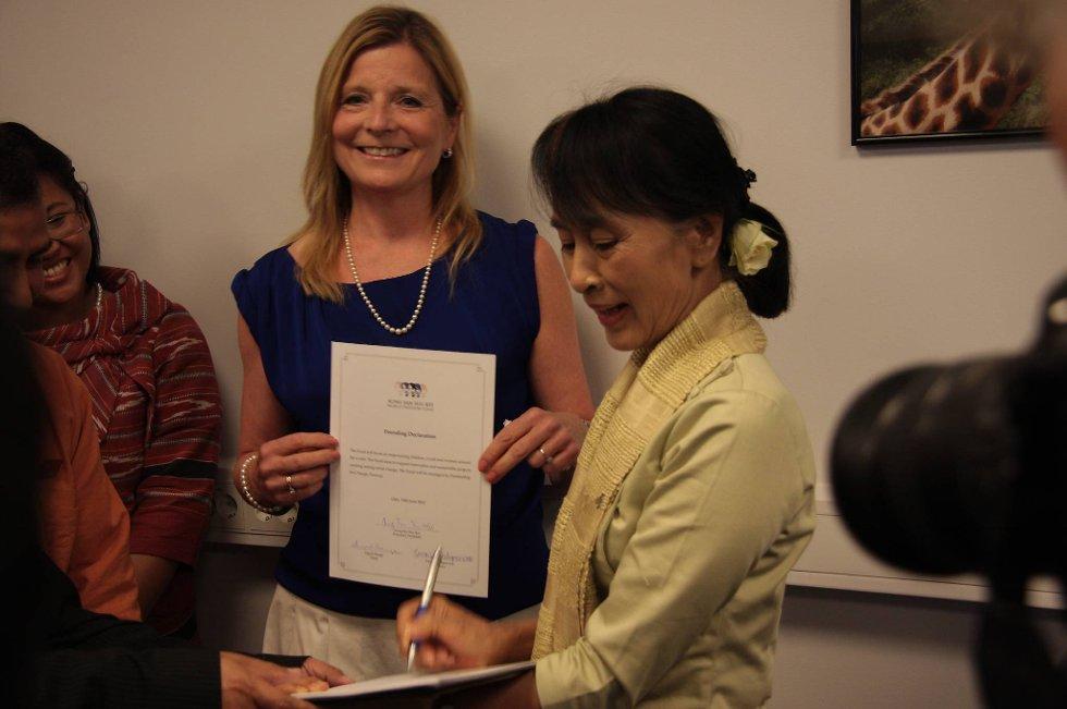 Aung San Suu Kyi signerer World Freedom Funds oppfordring til å gi bidrag store og små. I bakgrunnen Ingrid Stange, styreleder i stiftelsen Partnership for Change som er sekretariat for fondet. (Foto: Partnership for Change)