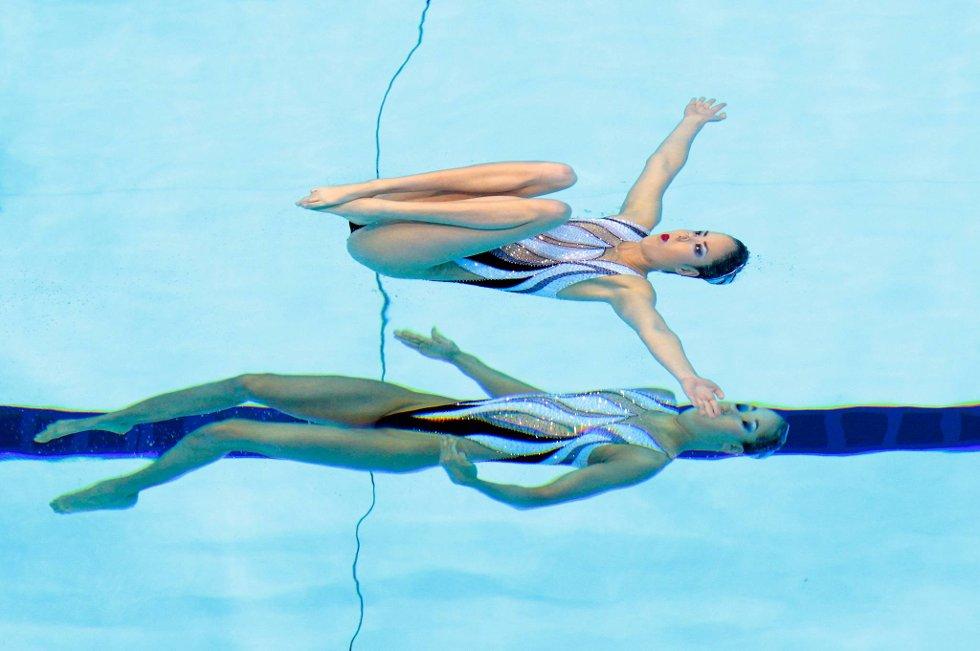 Hold munn, det er jeg som skal vise meg fram! Japanske Yukiko Inui og Chisa Kobayashi deltar i synkronsvømming. (Foto: Adam Pretty, Getty Images/All Over Press/ANB)