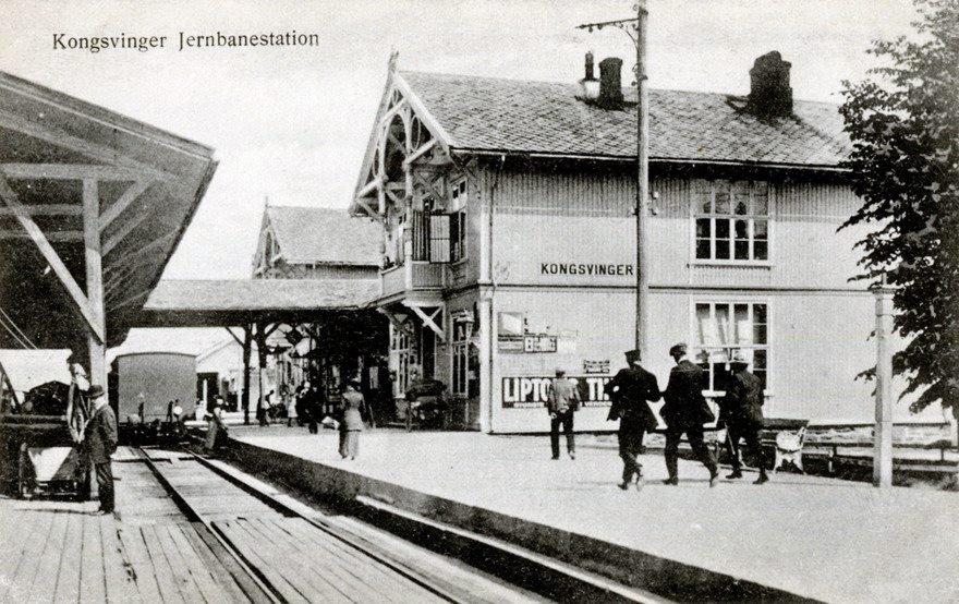 Må rekke toget: Bildet av Kongsvinger stasjon er fra tidlig på 1900-tallet. Togtabeller og klokka ble viktig, og konduktørene måtte spurte avgårde. Stasjonen hadde reklameplakat for ekslusiv Lipton te.      FRA NARVESENS POSTKORTSAMLING