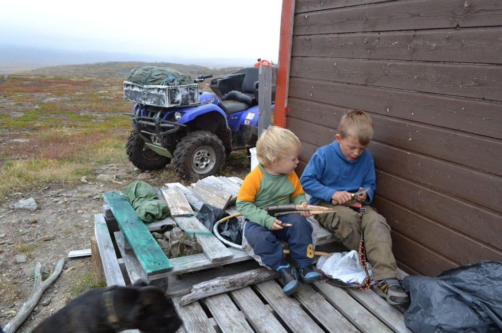 Nils Jovnna (7) er allerede en ivrig og rutinert reineier . Her lærer han lillebror Juhan Ailu (4) hvordan han skal bruke kniven til å spikke med.