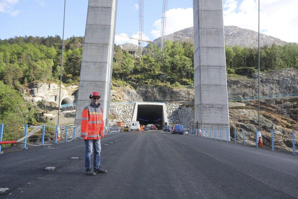 Prosjektleiar Øivind Søvik er fornøgd med det han ser på Hardangerbrua. I bakgrunnen er tunnelportalen på Bu. Gang- og sykkelveg kjem ut den mindre tunnelopninga til venstre i biletet, og fortset opp mot Buplatået.