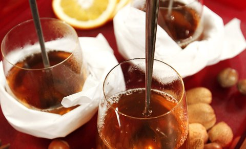 Rosiner, appelsinskiver og hakkede nøtter has i når gløggen er klar til servering.