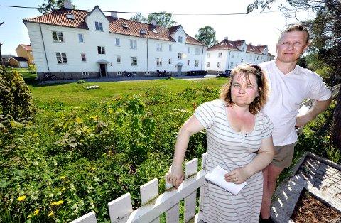 Rino Kristiansen og Gry Vågslid Gardsteig viser frem stedet hvor det kan bli nye hus – mellom gjerdet og den gamle bebyggelsen i Heibergs gate 1og 3.