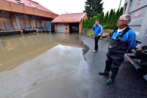 Tor Klausen (i vadebukse) og sønnen Pål, kunne slå fast at vannmassene har gjort stor skade i emballasjelageret.