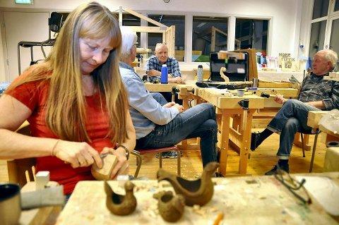 PRATER OG JOBBER: Det er minst like viktig med den sosiale biten som trearbeidet. Grete Strand Henriksen lager her ølhøner i forskjellige størrelser, men også mye annet.