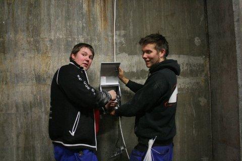 Stian Myrhaug og Christopher Teigstad monterer nye uttak for strøm til elbiler.