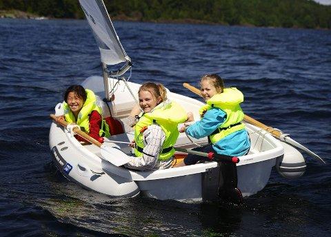 Maria Hovland (fra venstre), Maja Meyer og Annie Roer koser seg på sin første seiltur på Redningsselskapets sommerskole.
