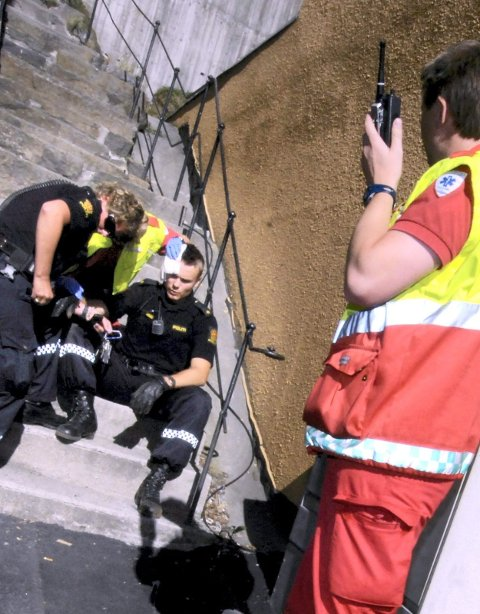En politibetjent i Arendal får medisinsk bistand etter at 23-åringen har slått ham i hodet med en planke. Foto Agderposten.