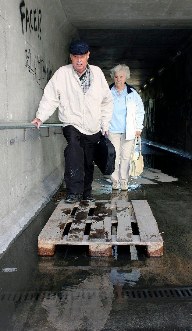 C-MOMENT: – Det er et C-moment å komme seg gjennom, sier Steinar Pedersen (74) og Betty Olsen (80), som bor i nærheten og har ufrivillig god trening i å skreve opp på pallen i dammen. FOTO: TRUDE BLÅSMO