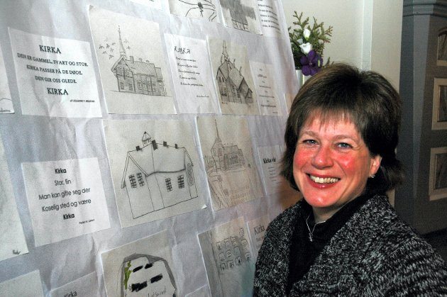 TEGNET: Sokneprest Merete Kavli er glad for at de yngste i bygda har fått være involvert i 100-årsjubileet. Tegninger og dikt som elever ved Lillemoen skole har laget, henger nå i kirken.