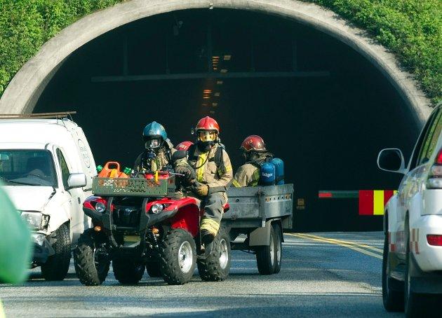 Brannmenn på vei ut av tunnelen. Tolv personer måtte på sykehus etter brannen.