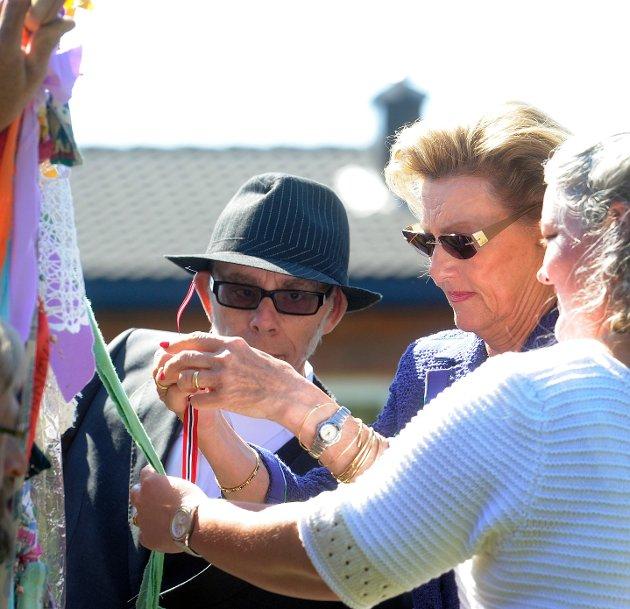 Dronningen knyter et sølvkors på fellesskapsteppet på Signo i Andebu. Teppet skal henges i Thomas-kirken.