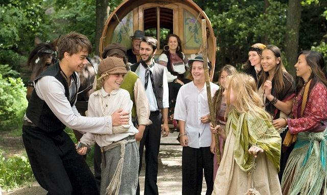 MYE LYS OG VARME: Det er mye smil og latter og blide fjes og sang og dans i «Yohan – Barnevandrer» som egentlig forteller historien om et tragisk kapittel i norsk historie; om utbyttingen av fattigfolks barn som tilnærmet slavearbeidere på slutten av 1800-tallet. Her fører sigøyner Alexander Rybak an i dansen, med hovedpersonen Yohan (Robin Daniel). Foto: Filmweb.no