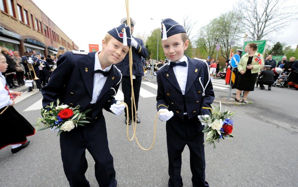 Kai Wilson (t.v.) og Sean Grimholt leder fanen til Sandefjord gutte- og jentekorps.