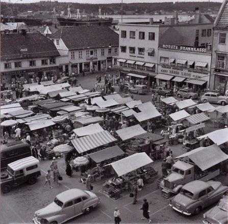 Slik så det ut på byens torv en sommerdag i 1956. Idag er det i beste fall en grønnsaksbod og en blomsterbod å se her, det meste av frukt og grønt er havnet under tak i byens supermarkeder.