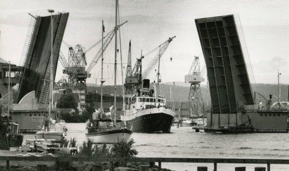 Kanalbroen åpnes en gang på 80-tallet, og slipper veteranskipet Kysten 1 ut mot træla. Kranene på Kaldnes mek. verksted ruver godt i bakgrunnen.