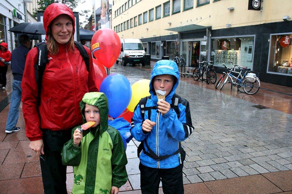 Tina Vestersager (f.v.) og sønnene Aksel og Mathias koser seg med is i regnværet. Nå håper de at været blir fint nok til å se på sandvolleyball på lørdag.