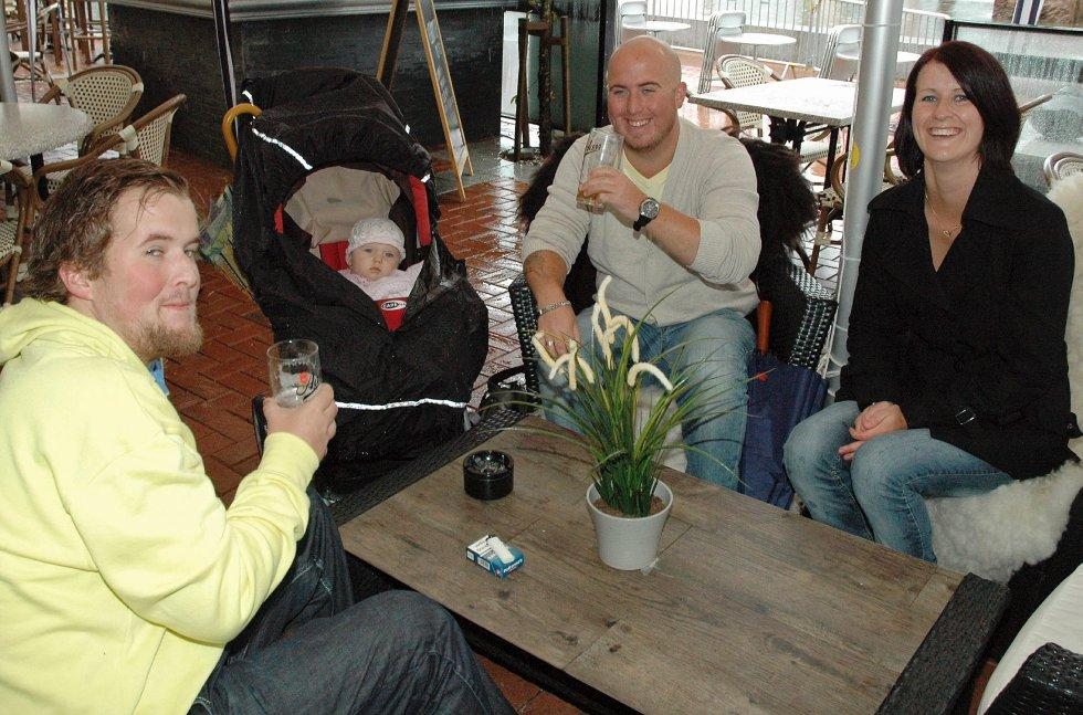 Kjetil Lersbryggen (til v) fra Drammen og sandeparet Håvard Lersbryggen og Mari Klufthaugen koser seg ute på Elvebredden. Der det er øl, er det håp, sier Kjetil.